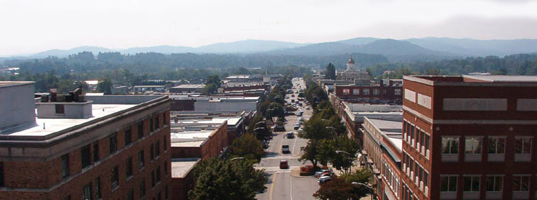 An aerial view of downtown Hendersonville's Main Street, with the Blue Ridge Mountains in the background.