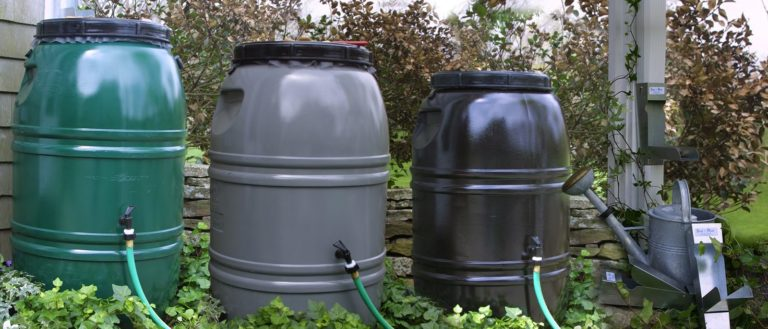 Storm water rain barrels in front of house.