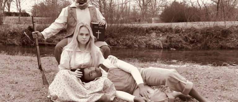 Brevard College Theatre students sitting on grass dressed in antique clothing for production of Brother Wolf.