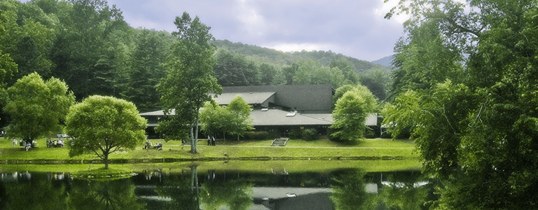 The exterior of Brevard Music College in front of a lake.
