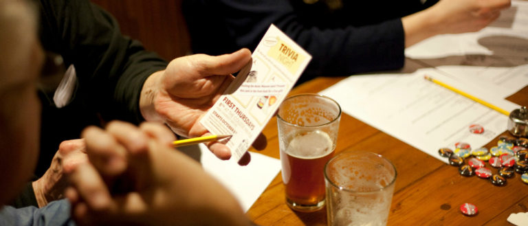 A group at a bar filling out a trivia card.